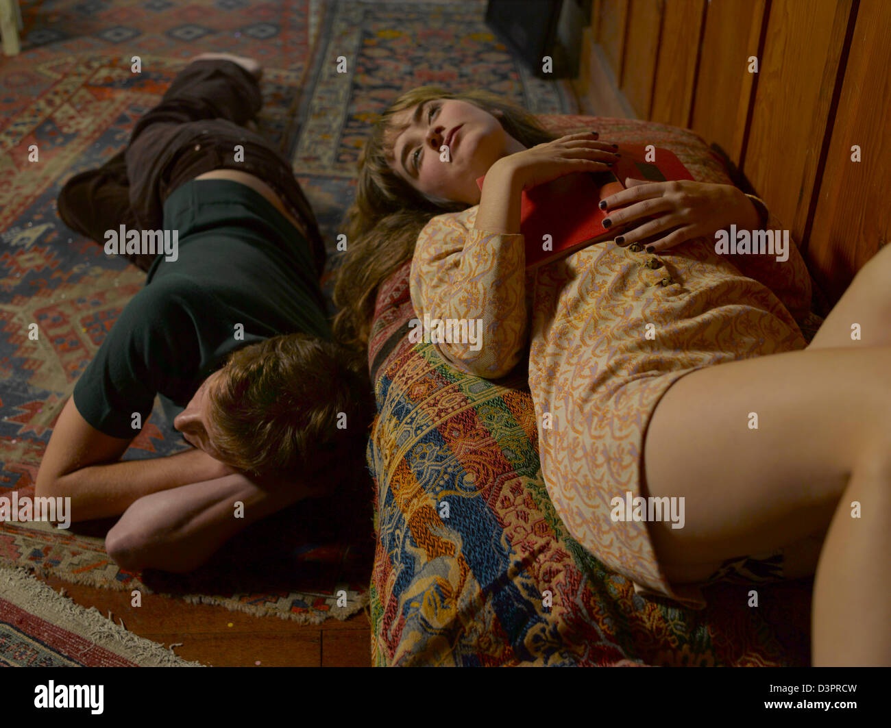 A boy and girl laying down on the ground together - Stock Image