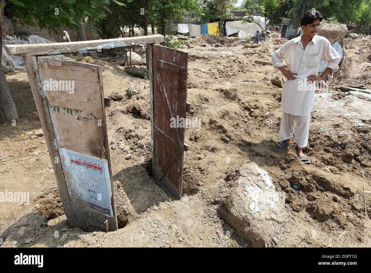 Charsadda, Pakistan, a man stands in front of the rest of his house after the flood disaster - Stock Image