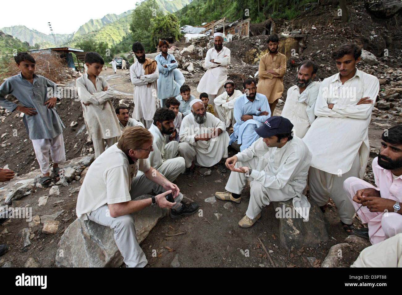 Kokarai, Pakistan, aid workers in discussion with residents - Stock Image