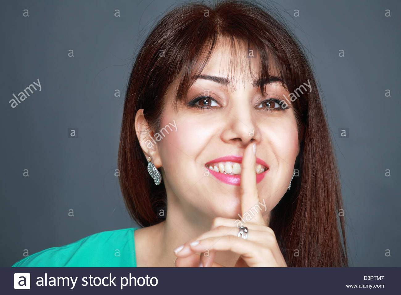 Smiling woman with finger on lips - Stock Image