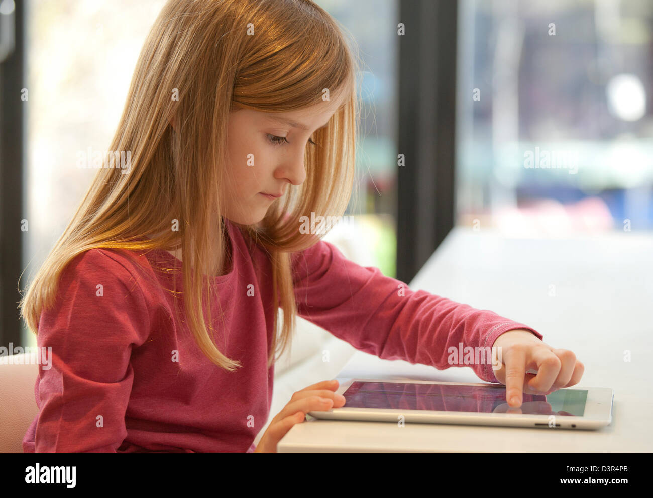 Young girl playing on an apple iPad tablet computer - Stock Image