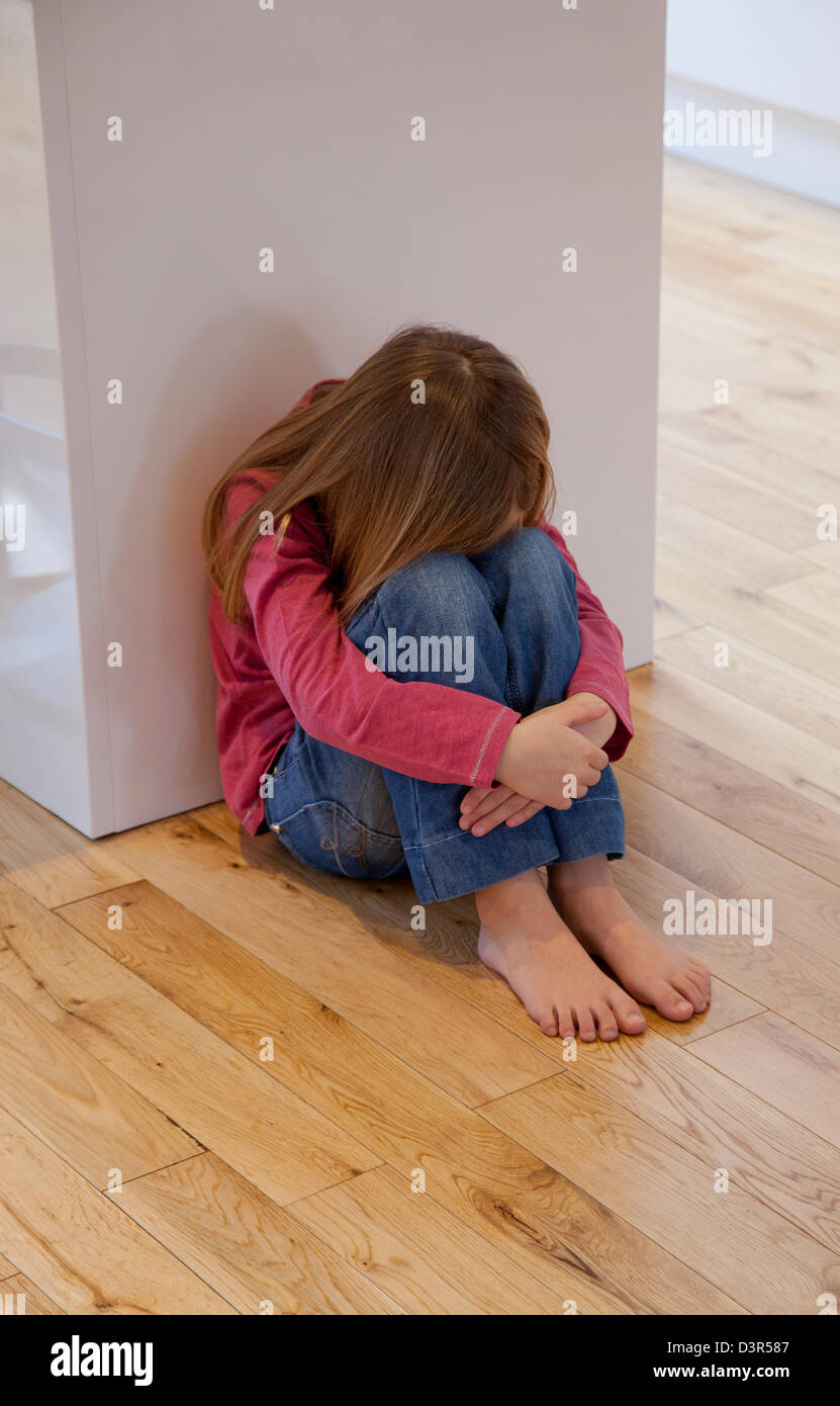 Young girl sat unhappy on the floor - Stock Image