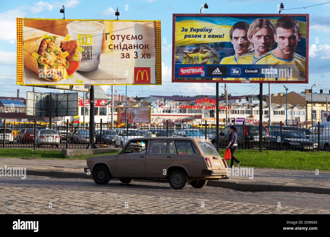 Lviv, Ukraine, a Lada drives past billboards - Stock Image