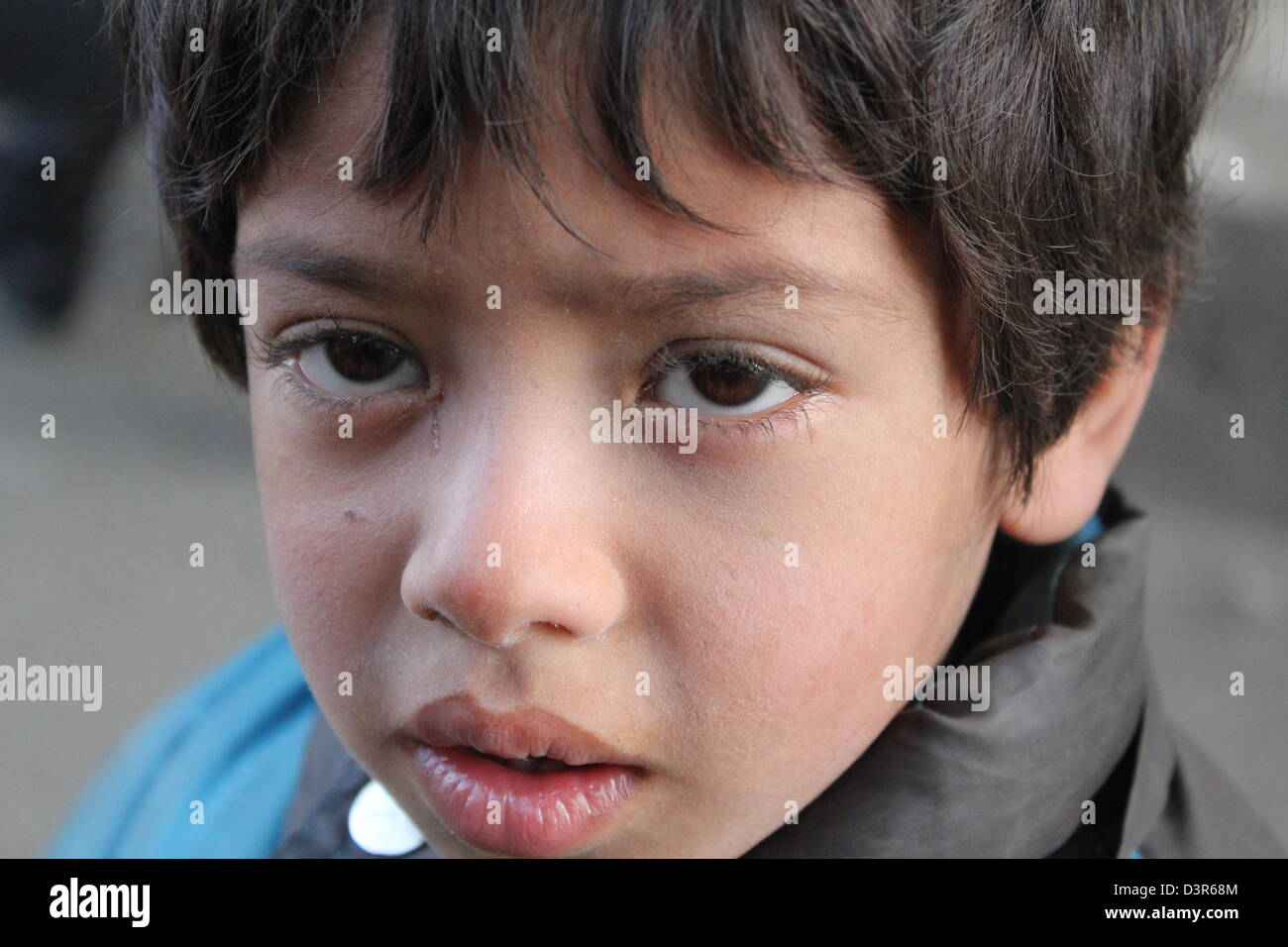A young boy begs for money outside of a market in Kabul, Afghanistan. - Stock Image