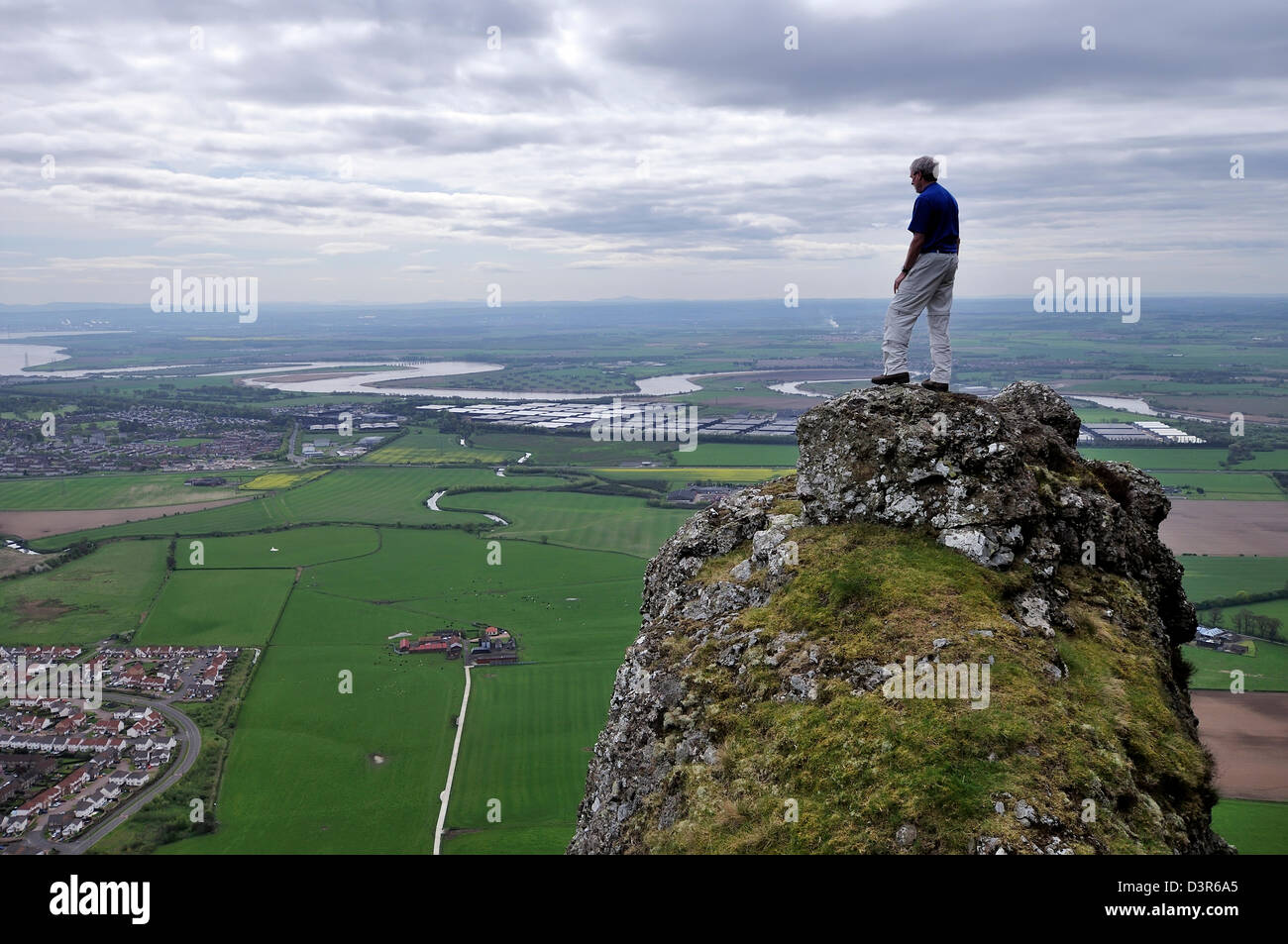 A hillwalker stands on a rock pinnacle and looks over the River Forth Stock Photo