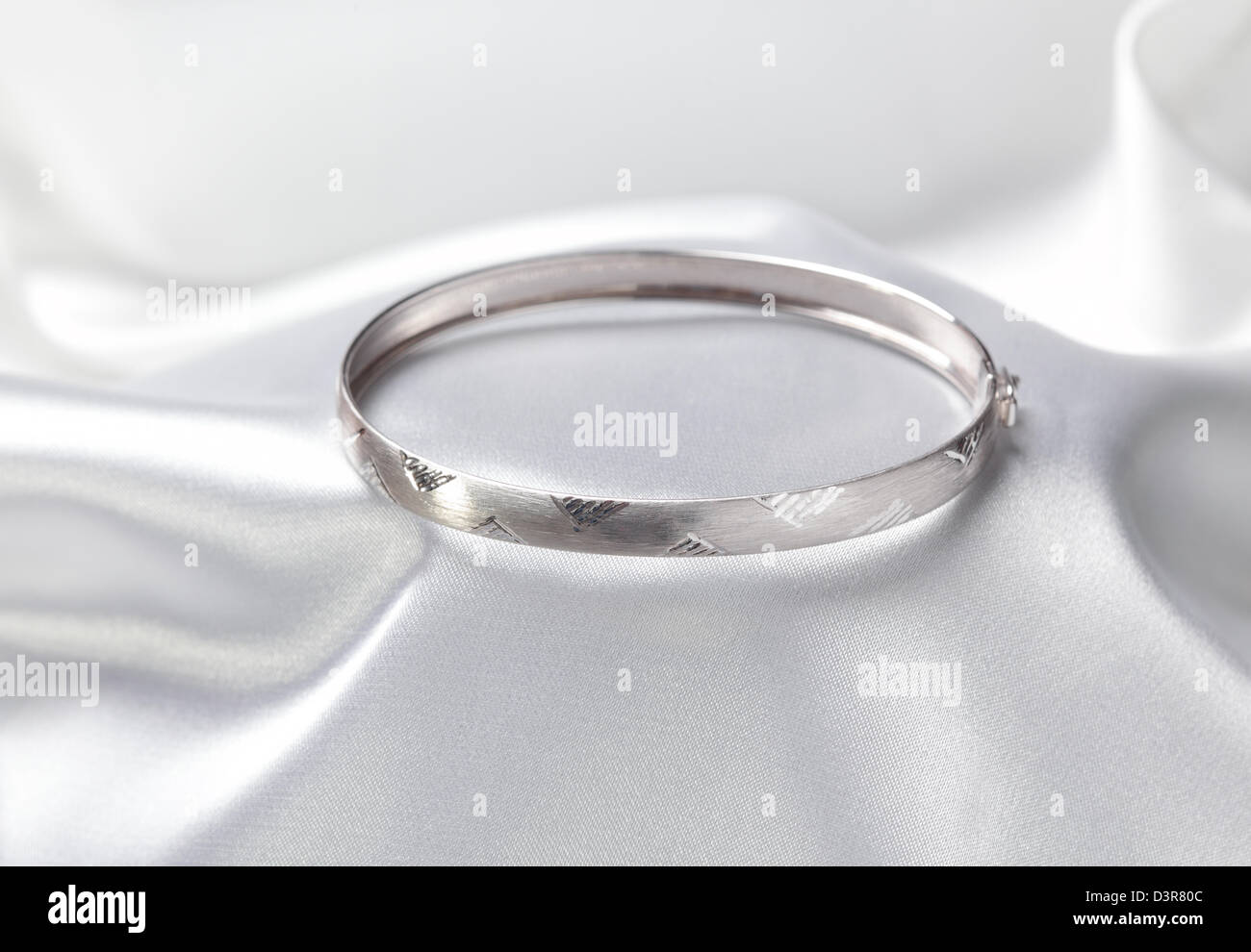 Close up photo of platinum or silver bracelet on white textile - Stock Image