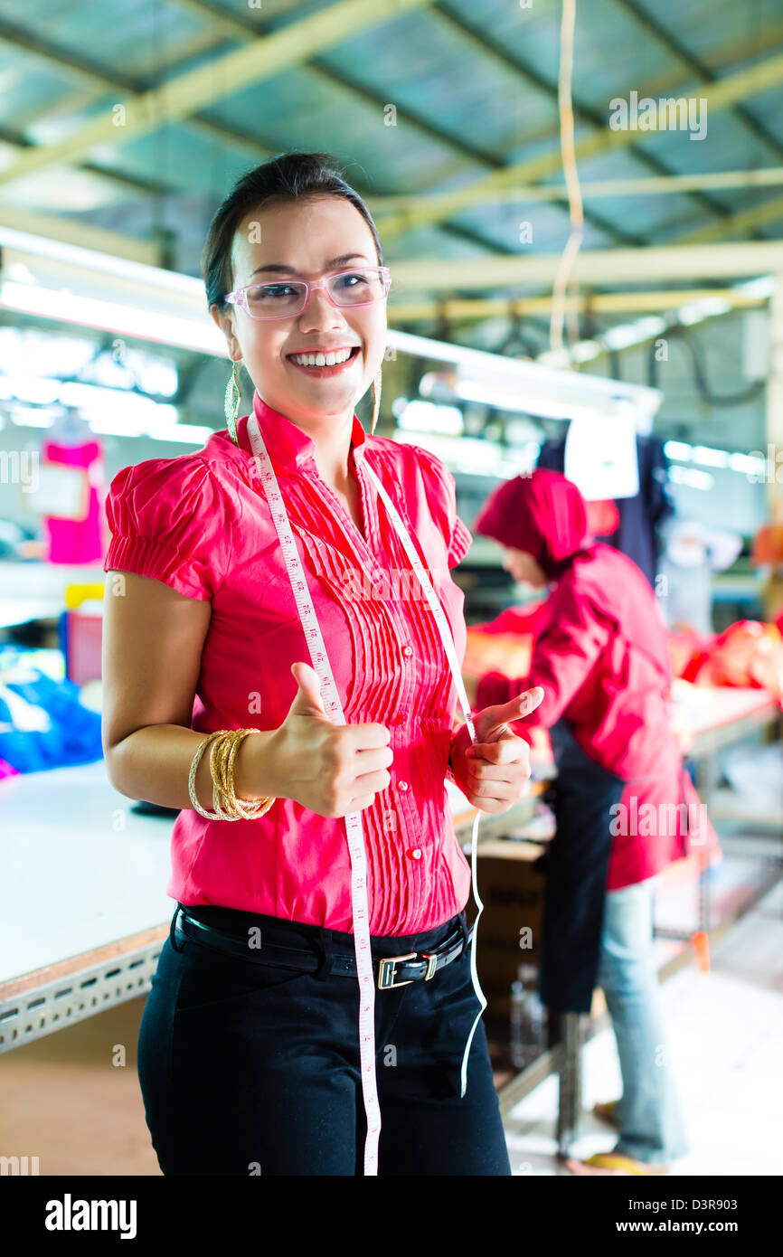 Female asian dressmaker or designer standing proudly in a textile factory, it is her workplace - Stock Image