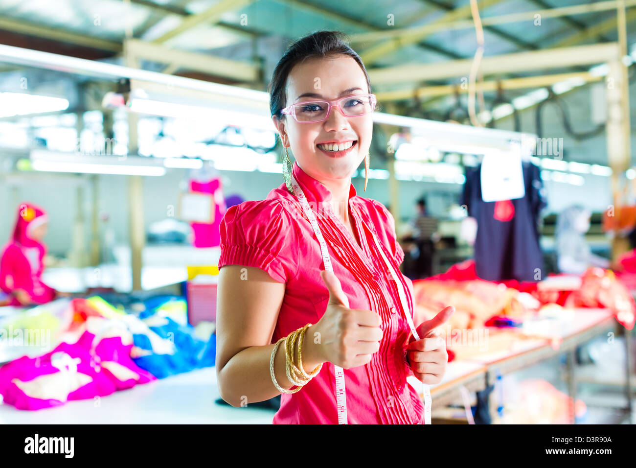 Female Chinese asian dressmaker or designer standing proudly in a textile factory, it is her workplace - Stock Image
