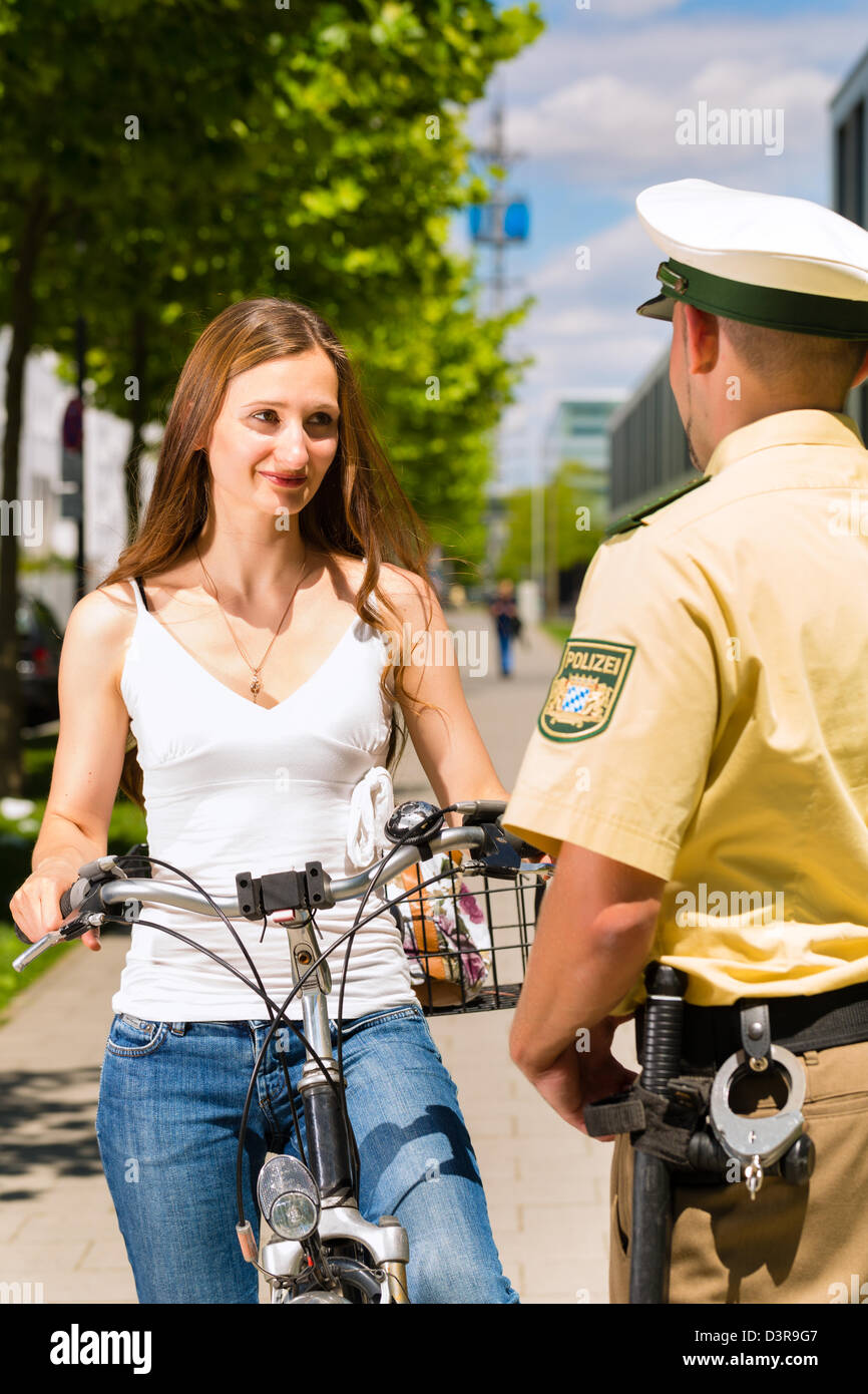Police - young woman on bicycle with police officer in traffic control - Stock Image