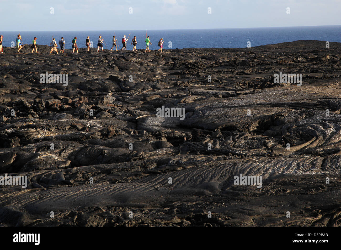 hikers on recent Pahoehoe lava from Kilauea Volcano Hawaii - Stock Image