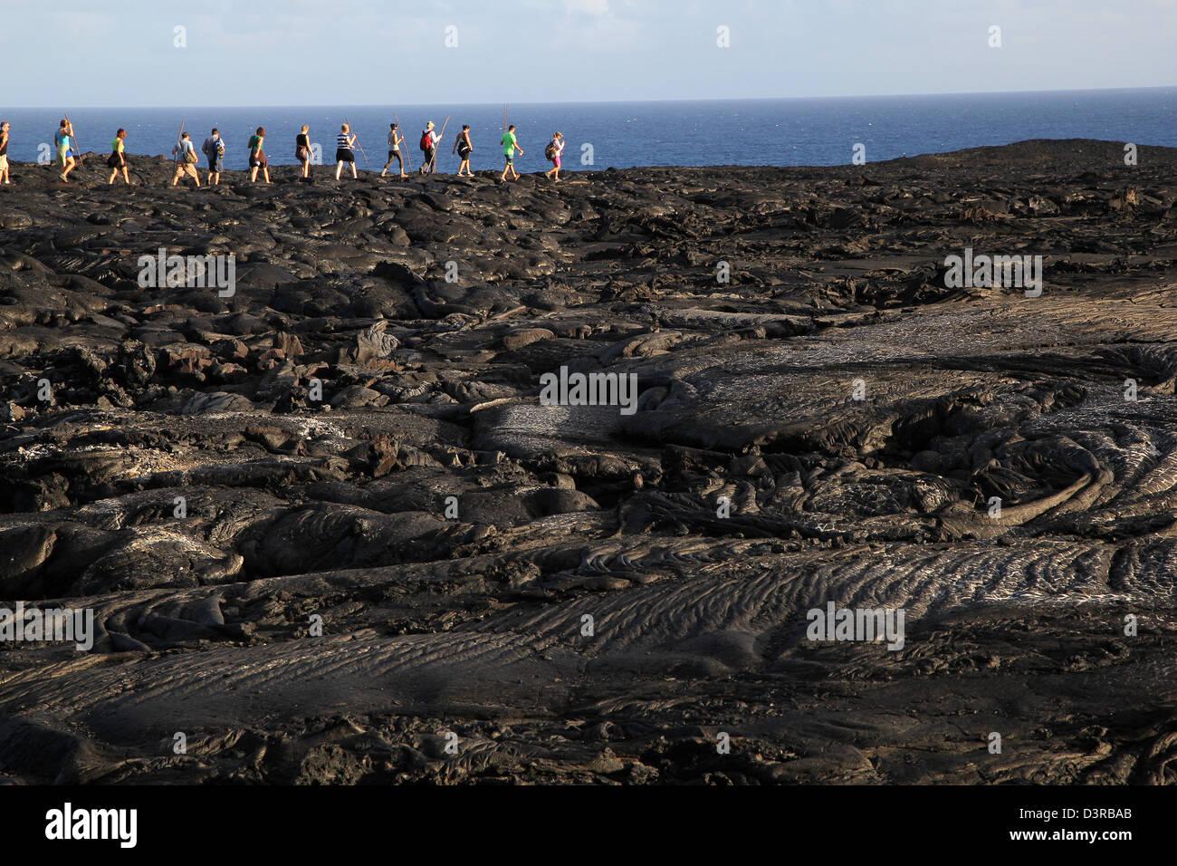 hikers on recent Pahoehoe lava from Kilauea Volcano Hawaii - Stock Image