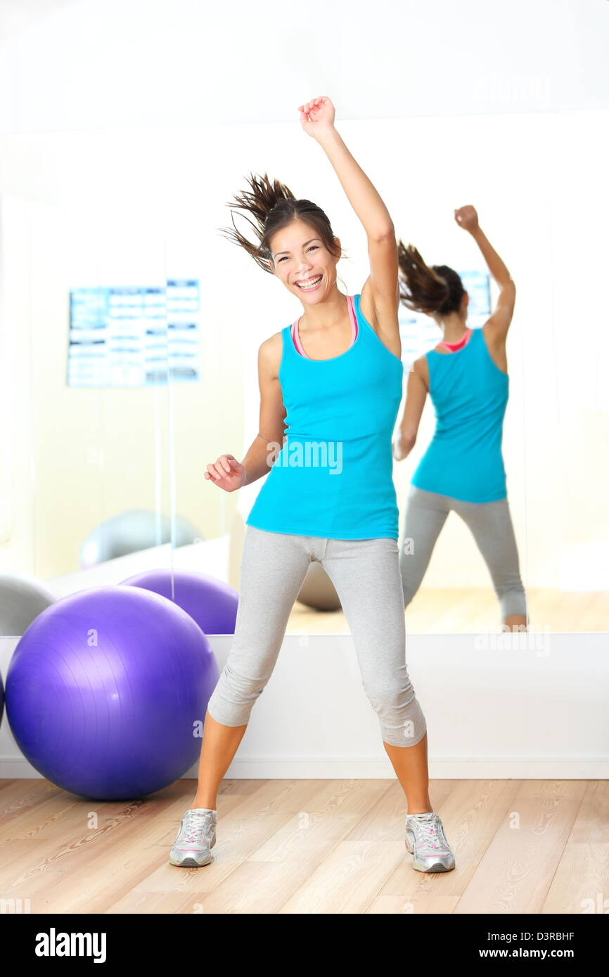 Young beautiful mixed race Caucasian / Chinese Asian woman dancing happy in fitness center - Stock Image