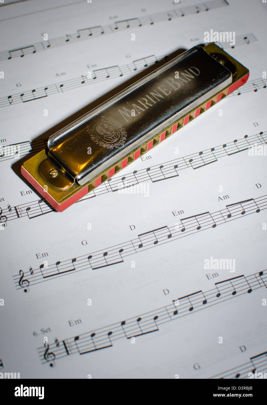 harmonica and note sheet - Stock Image