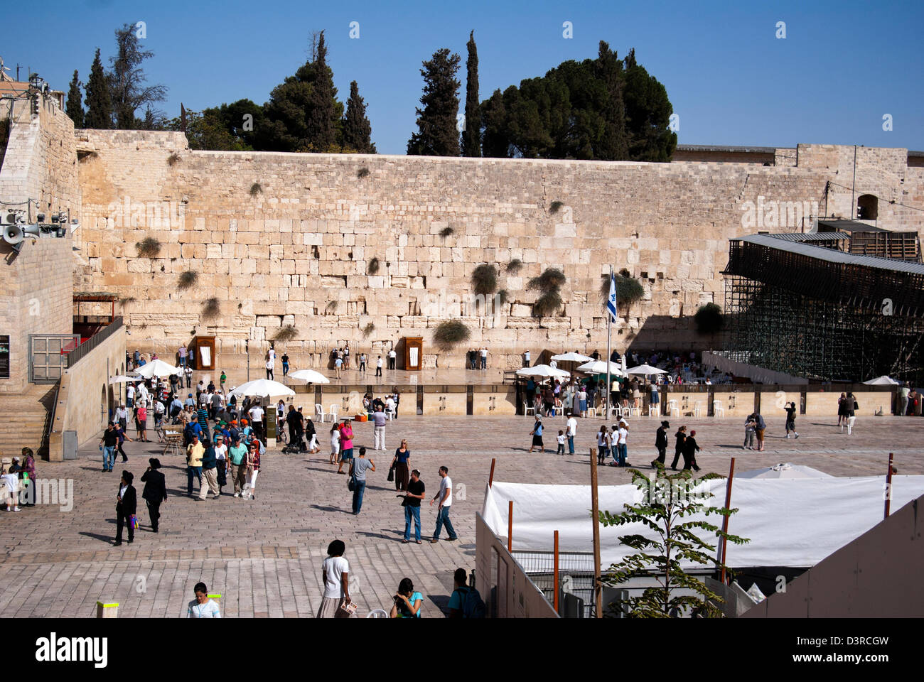 Wailing wall and people mingling outside the barrier Stock Photo