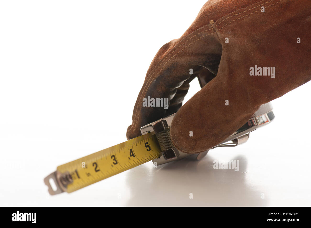 gloved hand holding steel tape measure - Stock Image