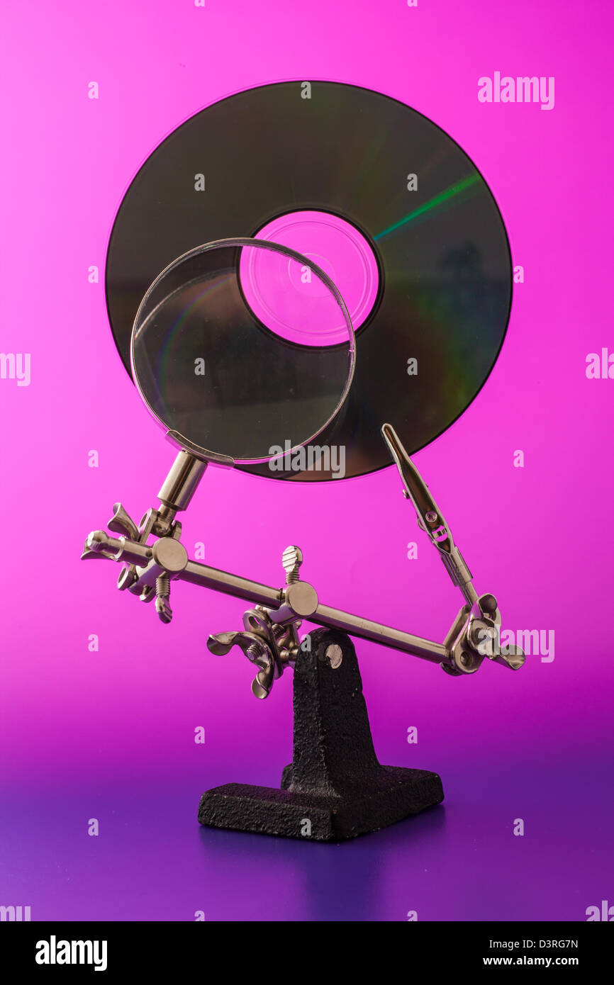 Concept for data analysis, CD and lens on a vivid colors background - Stock Image