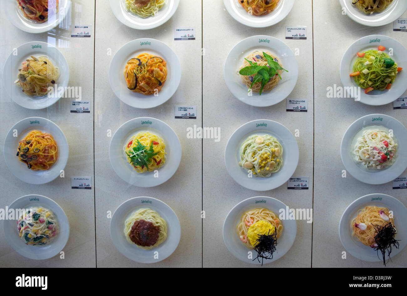 A unique restaurant menu window display with plates containing various spaghetti dishes mounted to a vertical wall. - Stock Image
