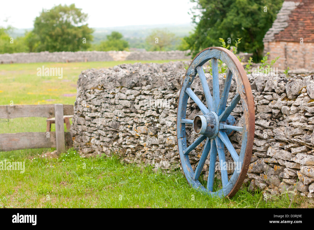 Old cartwheel resting on stone wall - Stock Image