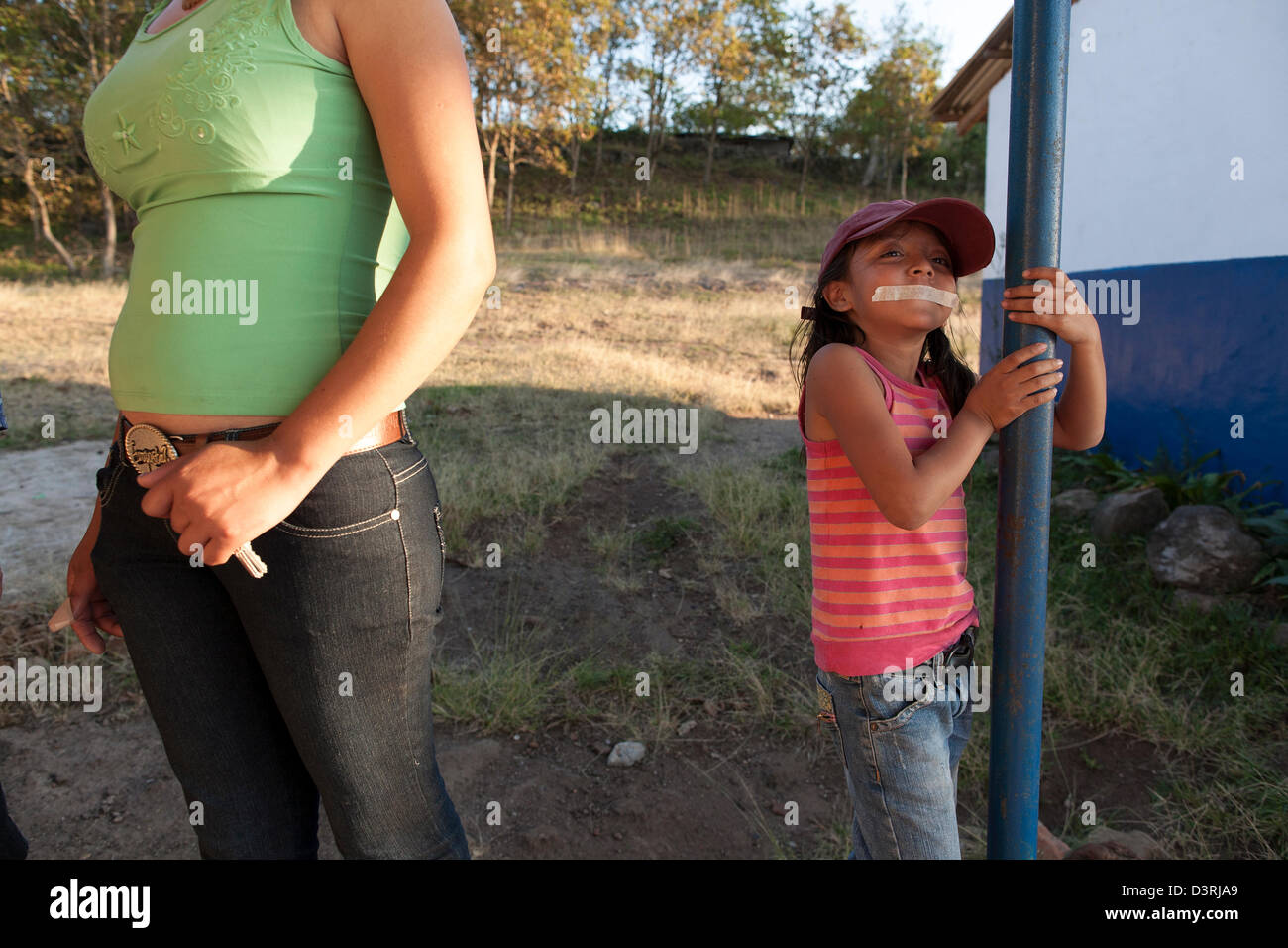 A young girl has her mouth taped and gagged for fun outside rural school in  Miraflores in coffee growing Nicaraguan Highlands