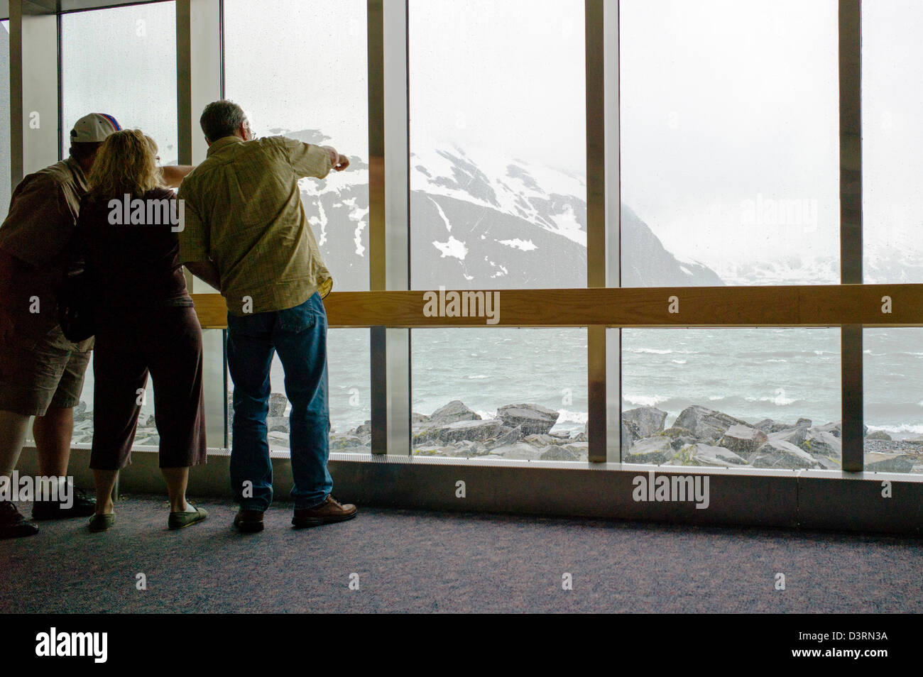 Tourist looks out large windows, Boggs Visitor Center, Portage Lake, Portage Glacier, Chugach National Forest, Portage, - Stock Image