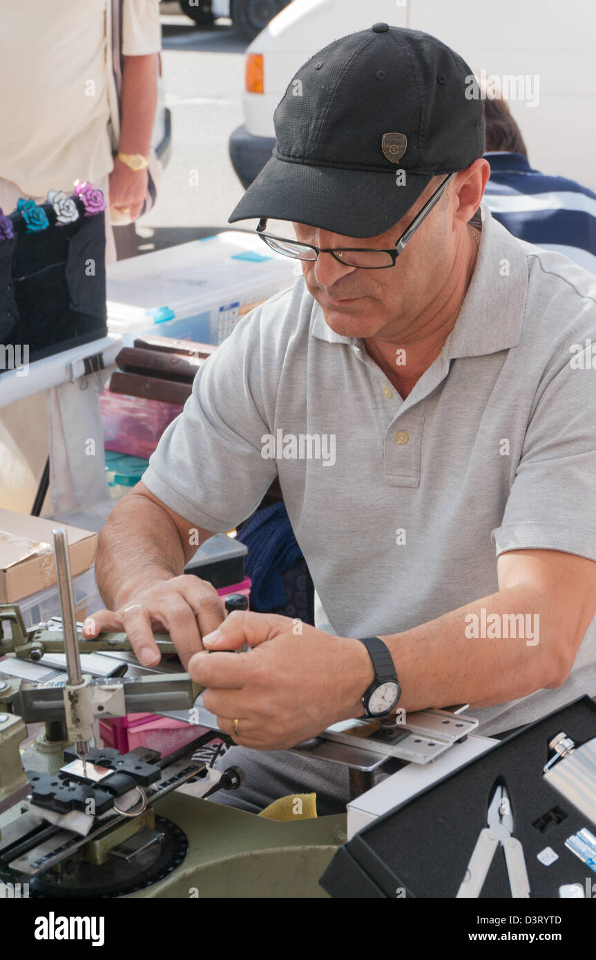 Engraver at work within the open air market at Puerto de Mogan, Gran Canaria - Stock Image