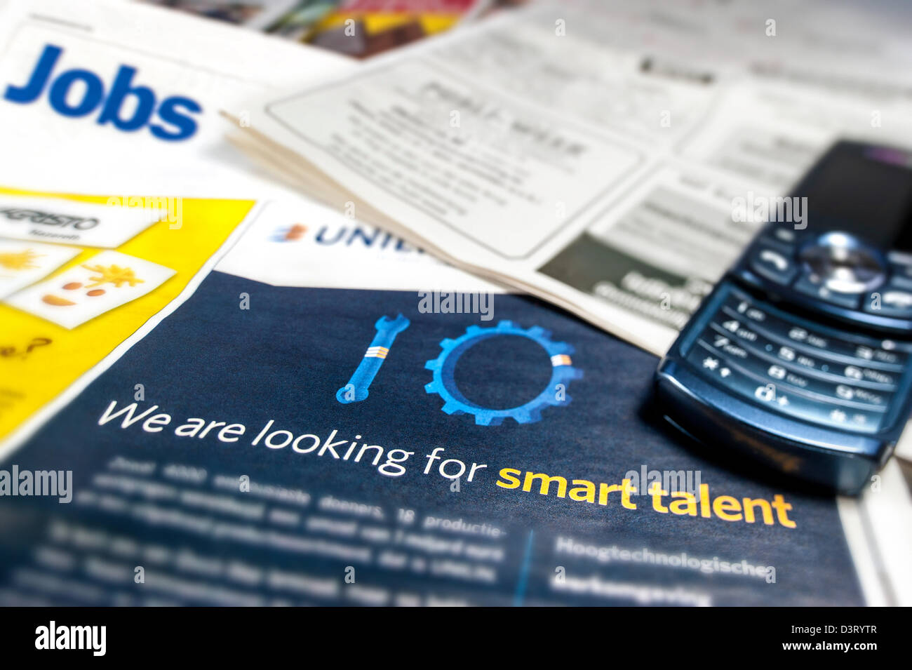Cell phone and advertisements for jobs for unemployed workers on employment page in newspapers - Stock Image