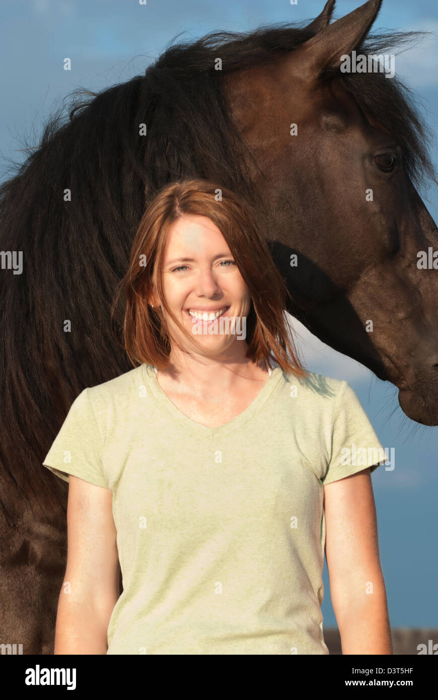 Woman horse trainer in front of large black animal, smiling, happy, and confident horsewoman portrait in sunlight. - Stock Image