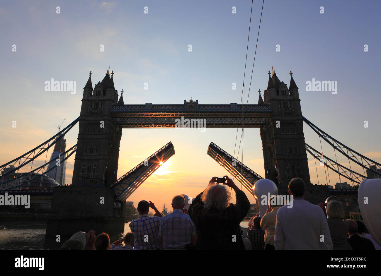Tourists photographing Tower Bridge at sunset from a boat on the River Thames London England UK GB Taking a photo - Stock Image