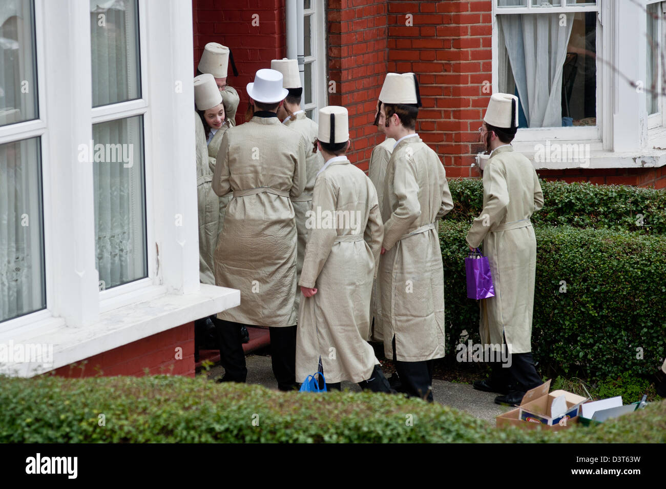 London, UK - 24 February 2013: a group of young Orthodox Jewish boys enter the house of a family in Stamford Hill - Stock Image