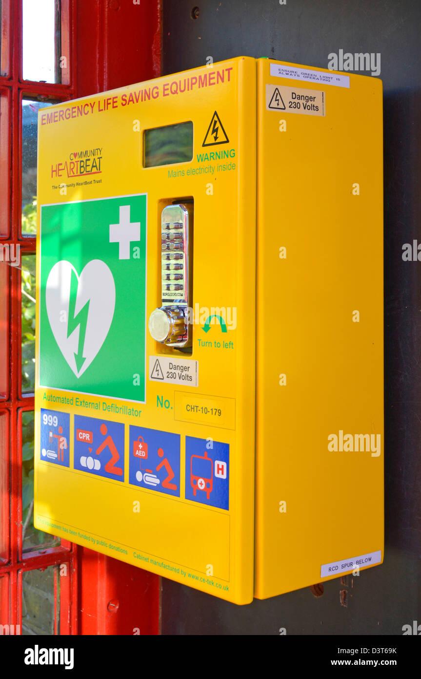 Heart attack emergency life saving defibrillator equipment housed inside redundant red K6 telephone phone box kiosk - Stock Image