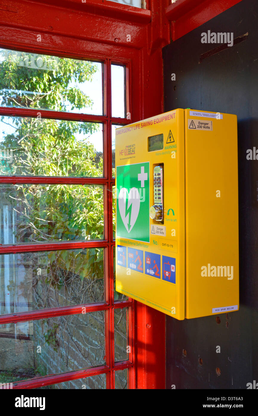 Emergency defibrillator housed inside redundant red K6 telephone phone box kiosk located in the centre of a village - Stock Image