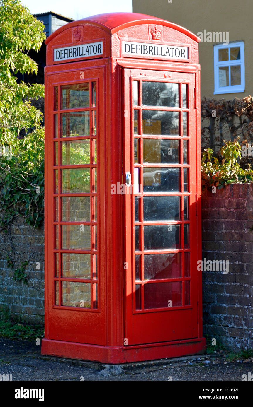 Defibrillator housed inside redundant red K6 telephone phone box kiosk located in the centre of a village community - Stock Image