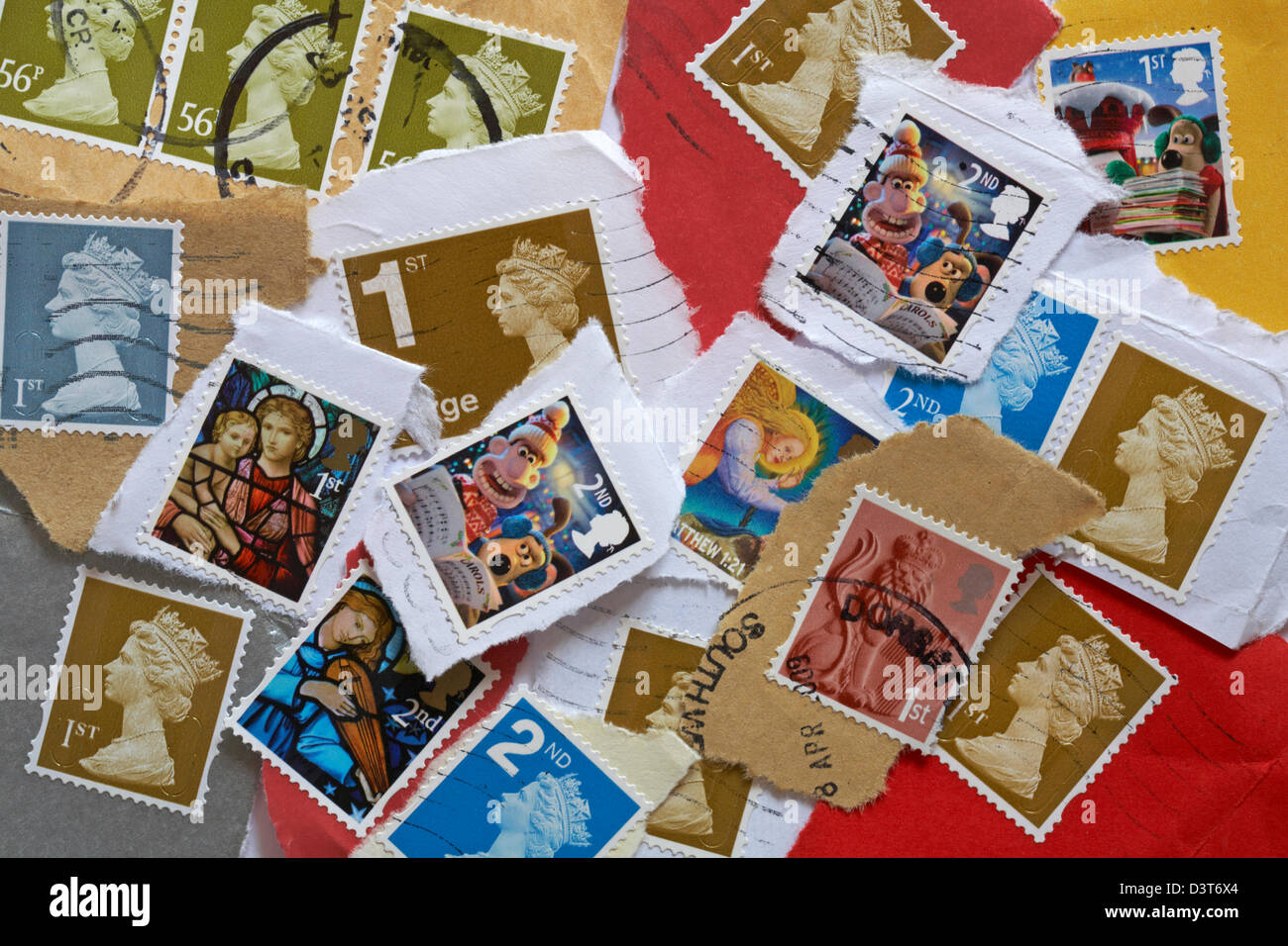 pile of used British postage stamps torn off envelopes and postcards - Stock Image
