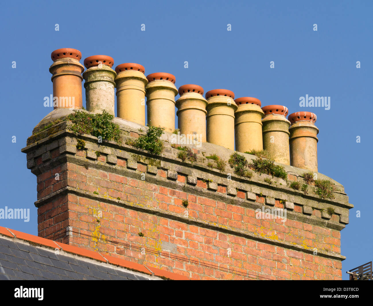 Row of chimney pots on a house roof in Penzance, Cornwall UK. - Stock Image