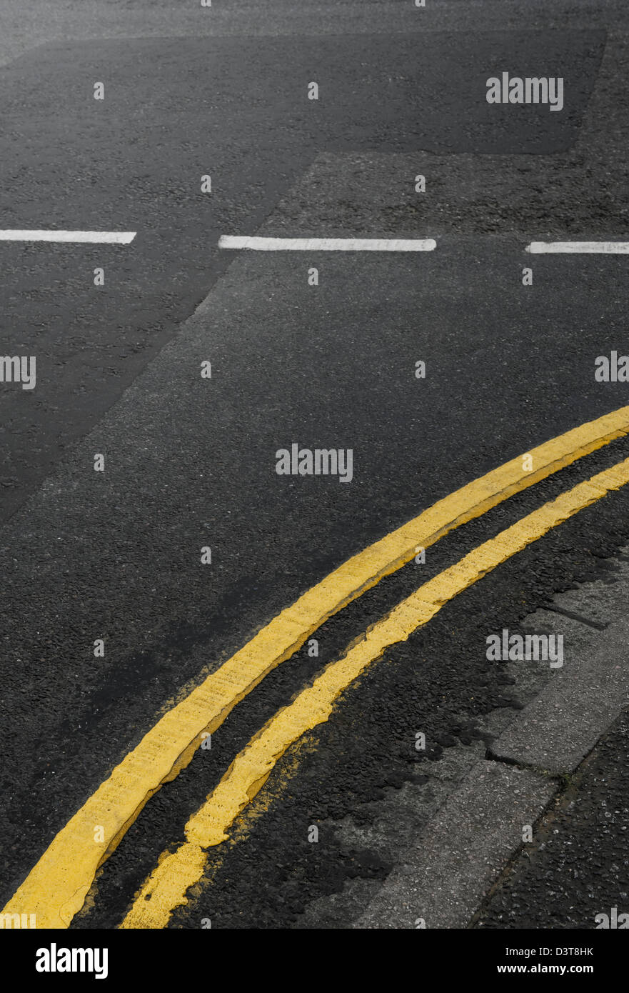 Curved Double Yellow Lines on the Road at a Junction, UK - Stock Image