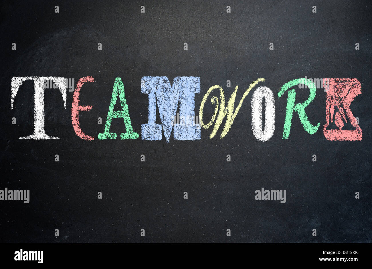 Working together concept, teamwork written with various letter fonts on a blackboard - Stock Image