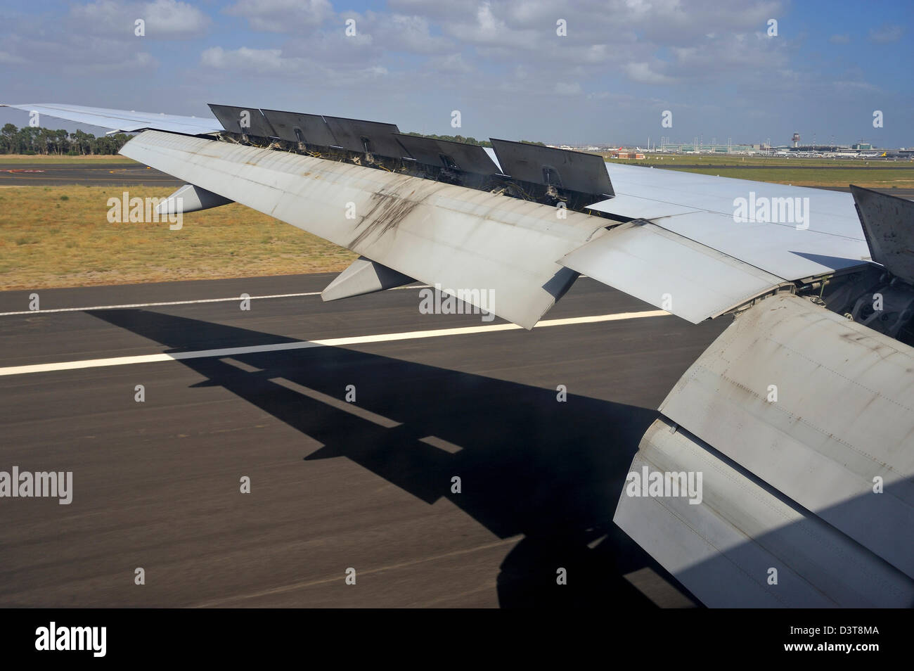 Wing of an aircraft landing on an airport runway - Stock Image