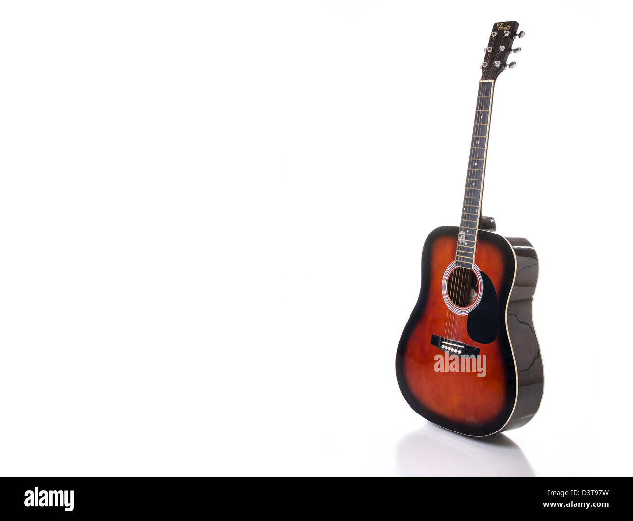 An acoustic guitar set against a white background, and reflecting in the surface below. - Stock Image