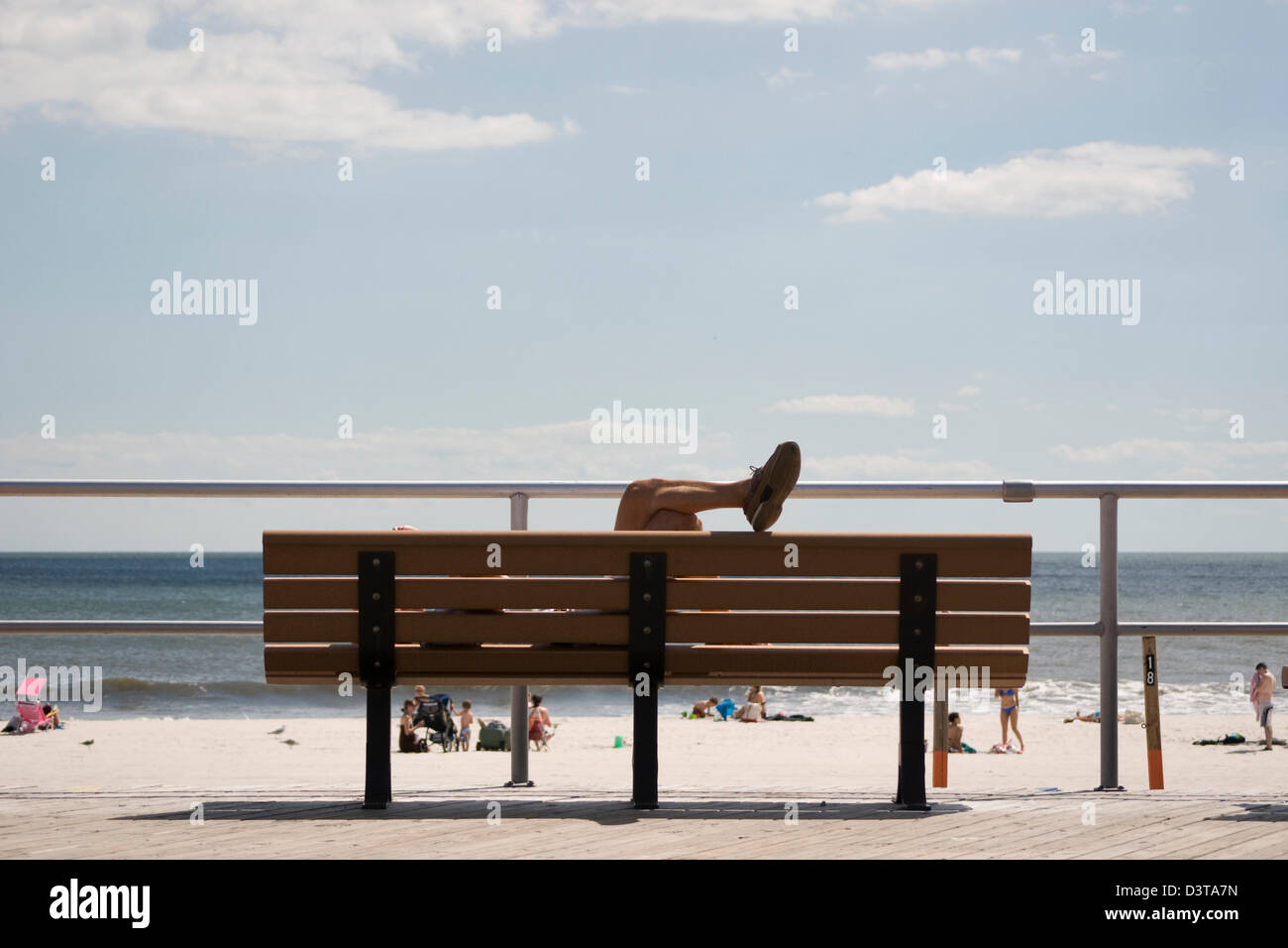 A beach-goer relaxes on a Long Beach, New York boardwalk bench. - Stock Image