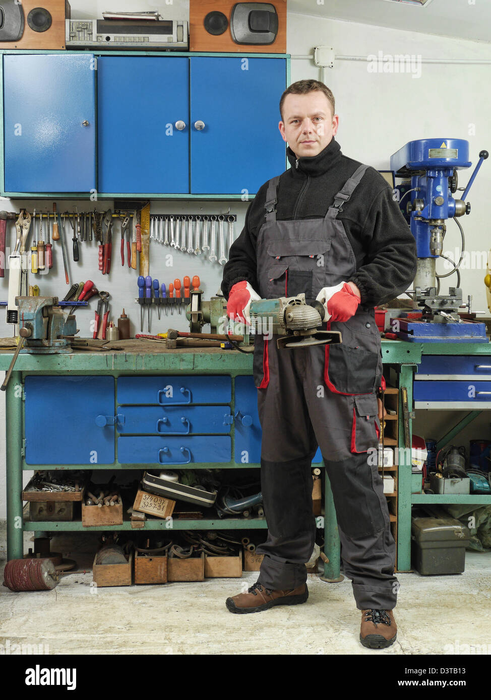 Locksmith holding angular grinder while posing in his workshop - Stock Image