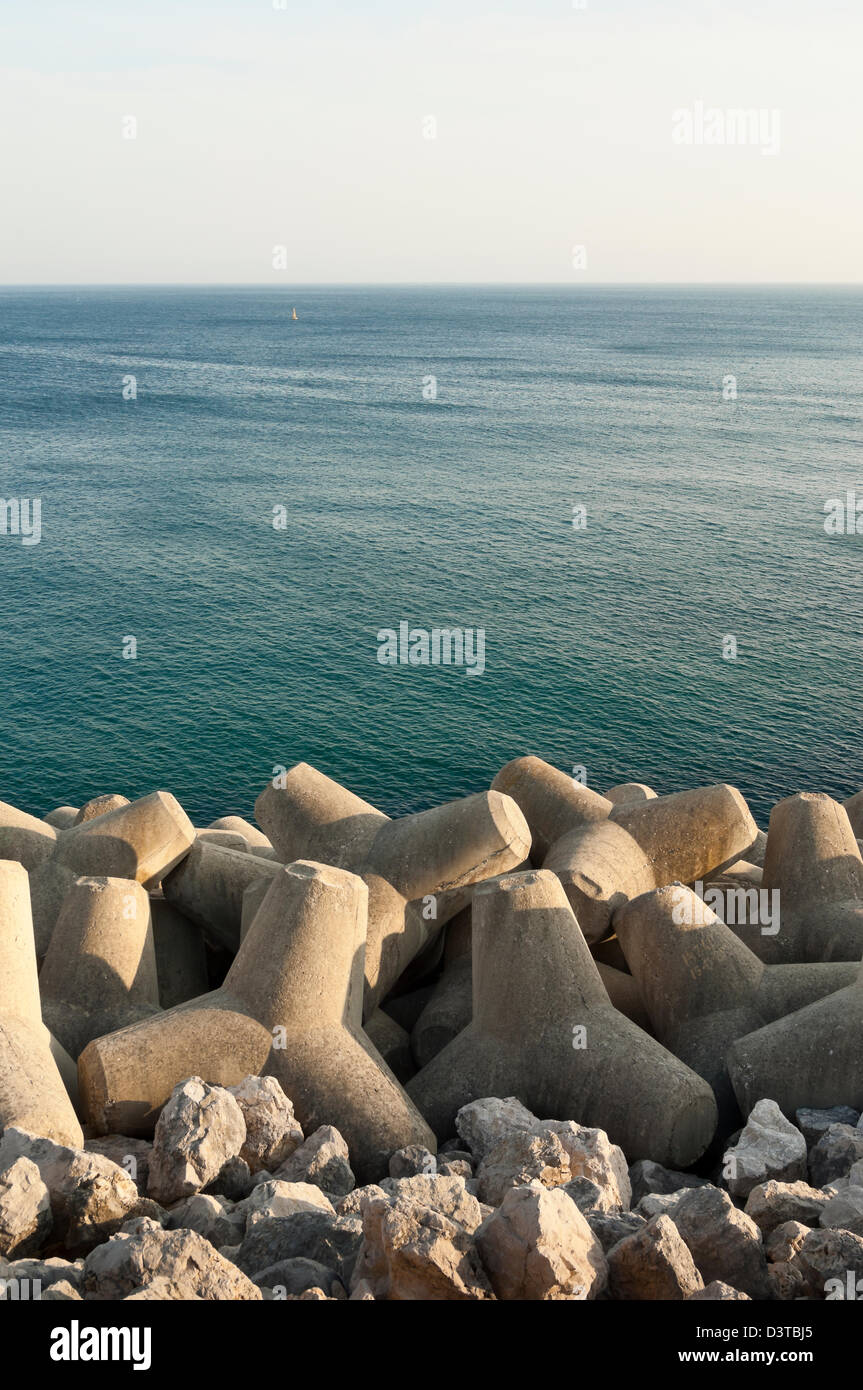 Concrete tetrapod breakwater in the shore near Sesimbra, Portugal - Stock Image