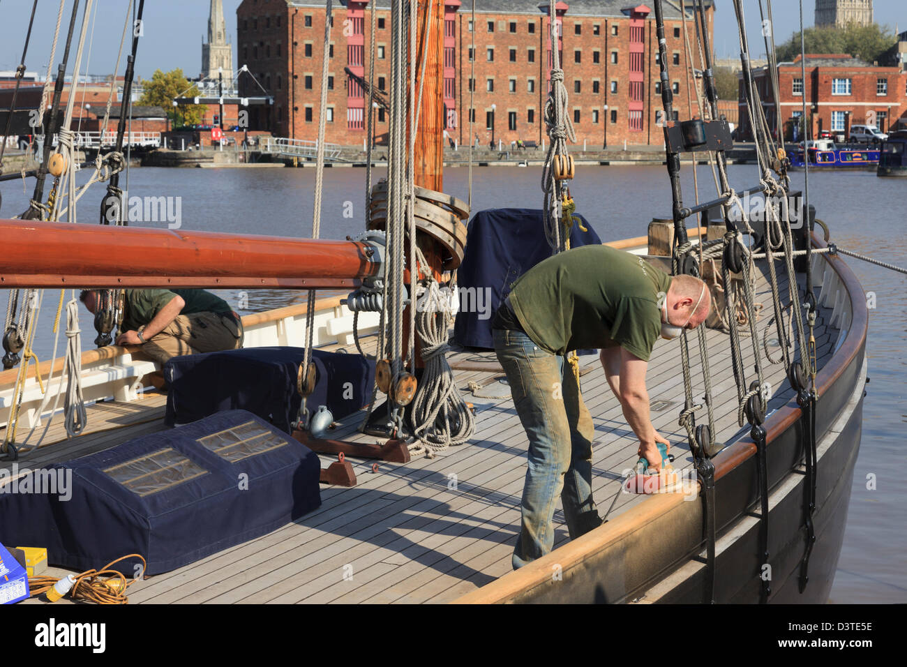 Man sanding wooden deck restoring a classic ship in the boatyard at Gloucester Docks, Gloucestershire, England, - Stock Image