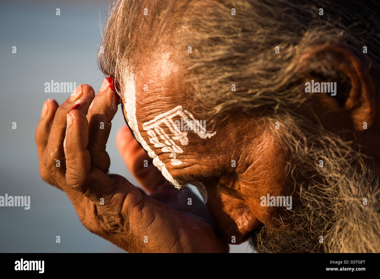 Sadhu painting his face with the word for God on his forehead at the Kumbh Mela, Allahabad, India - Stock Image