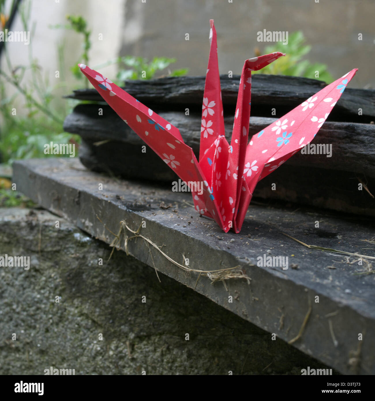 Red paper crane placed outdoors on a slab of slate - Stock Image