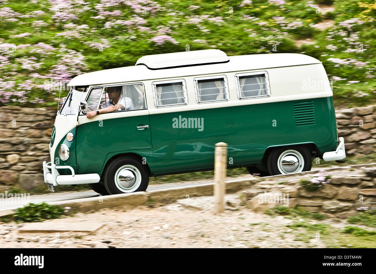 Green VW campervan on coastal road, St Agnes, Cornwall, UK - Stock Image