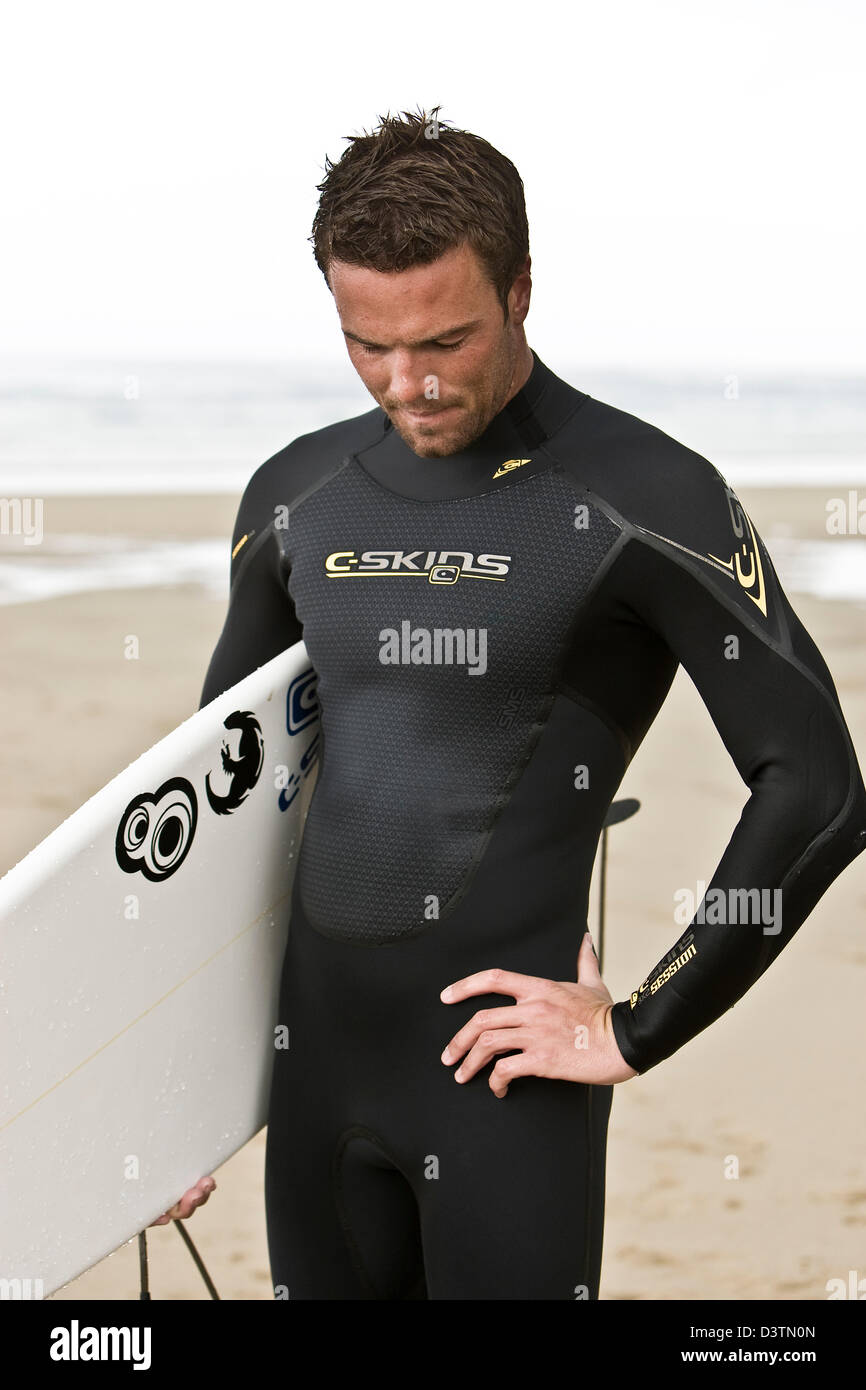 Surfer stands with board looking down, St Agnes, Cornwall, UK - Stock Image