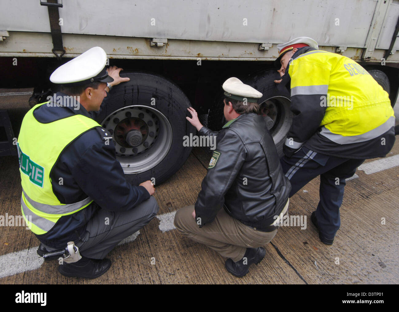 Police officers from (L-R) Czech Republic, Germany and Austria inspect a truck on a autobahn A3 rest area near Ruhstorf, - Stock Image