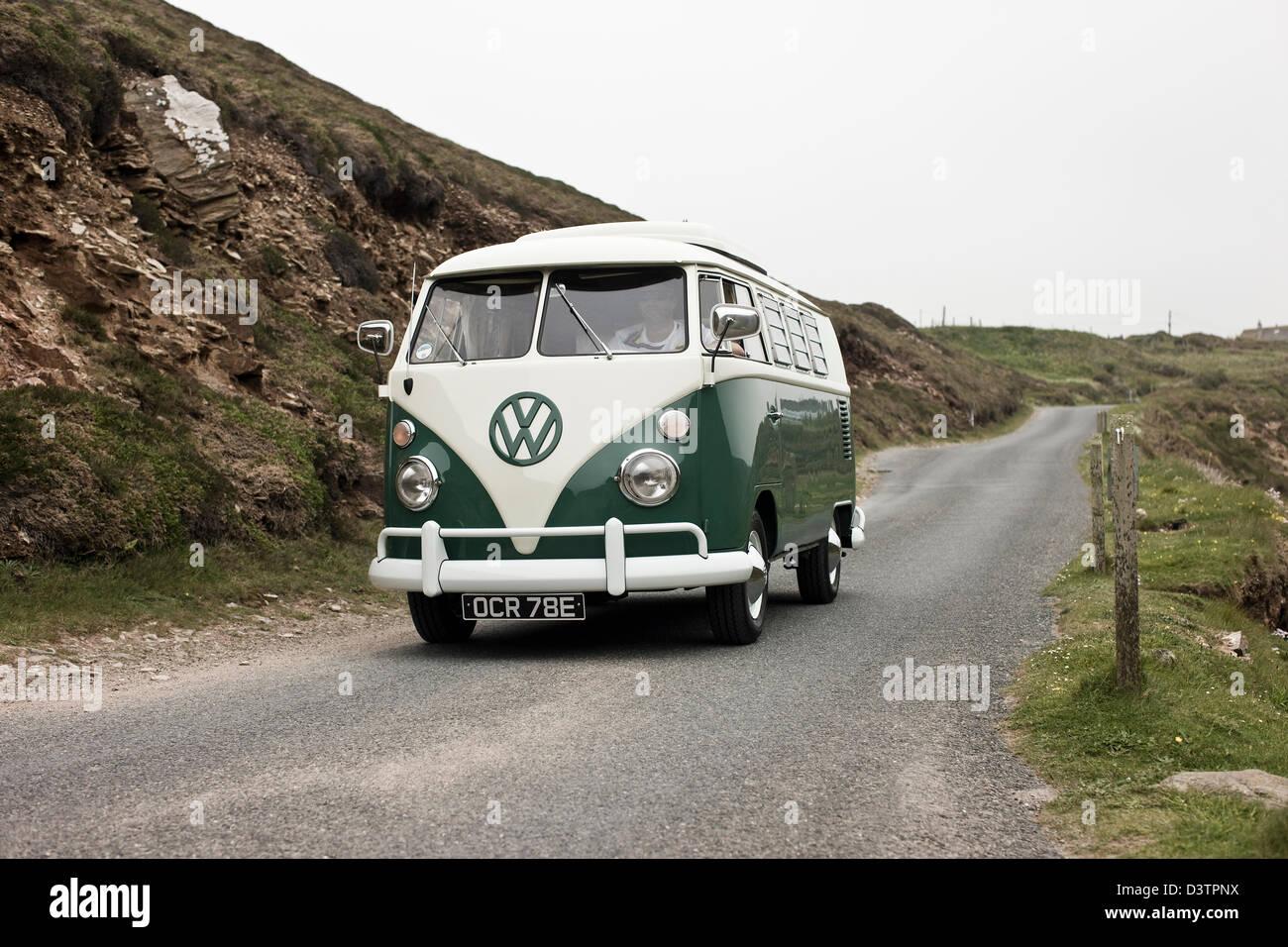 VW campervan on coastal road, St Agnes, Cornwall, UK - Stock Image