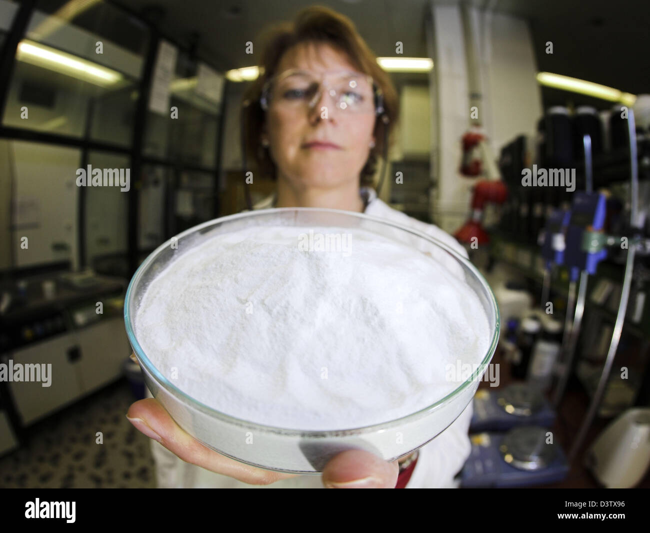 A chemist presents a cup of Aerosil R 812 S powder in the