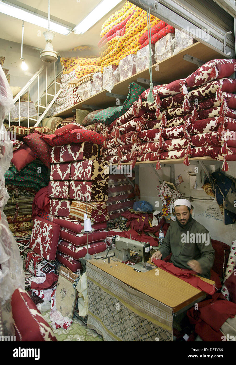 A tailor manufactures all sorts of covers for cushions in a souk of